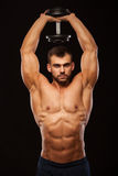 Strong man making exercises on triceps with a dumbbell. Close up shot training hands. Fitness Model showing his Torso. With six pack abs. isolated on black Royalty Free Stock Photos