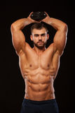 Strong man making exercises on triceps with a dumbbell. Close up shot training hands. Fitness Model showing his Torso. With six pack abs. isolated on black Stock Photography