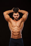 Strong man making exercises on triceps with a dumbbell. Close up shot training hands. Fitness Model showing his Torso. With six pack abs. isolated on black Stock Photos