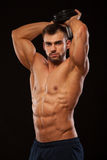 Strong man making exercises on triceps with a dumbbell. Close up shot training hands. Fitness Model showing his Torso. With six pack abs. isolated on black Royalty Free Stock Image