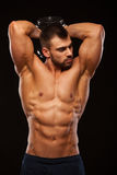 Strong man making exercises on triceps with a dumbbell. Close up shot training hands. Fitness Model showing his Torso. With six pack abs. isolated on black Stock Images