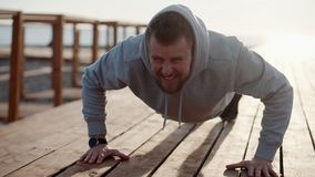 Strong man is making pushups outdoors in sunny morning stock video footage