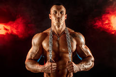 Strong man with metal chain. Smoky background Royalty Free Stock Photography