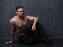 Strong man with a naked torso in black pants and boots royalty free stock photo