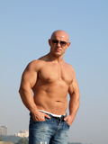 Strong man with nude torso. Strong muscular man in sunglasses with nude torso Stock Image