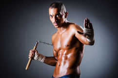 Strong man with nunchaku. On black Stock Photos