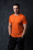 Strong man in an orange shirt tucked hands in his pockets stock images