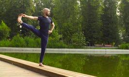 Strong man performing one-leg standing balance Stock Photos