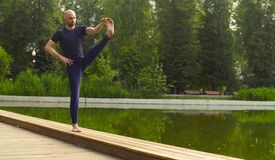 Strong man performing one-leg standing balance Stock Images