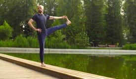 Strong man performing one-leg standing balance Stock Image