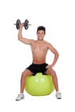 Strong man practicing exercises with dumbbells sit on a ball Royalty Free Stock Image