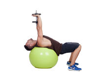 Strong man practicing exercises with dumbbells sit on a ball Royalty Free Stock Photography