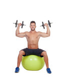 Strong man practicing exercises with dumbbells sit on a ball Royalty Free Stock Photo