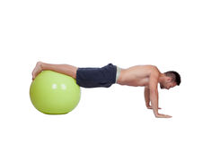 Strong man practicing pushups with a big ball Stock Photography