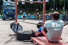 Strong man pulling  heavy truck with a rope. Almaty , Kazakhstan - May 28, 2017. strong man pulling  heavy truck with a rope  City fesitwal sport on the street Royalty Free Stock Photo