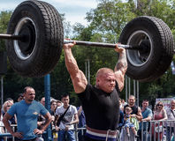 Strong man raises a heavy barbell. Weightlifting royalty free stock photos