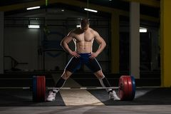 Powerlifter Heavy Weight Barbell Exercise Deadlift in Powerlifti. Strong Man Ready to Lift Heavy Barbell From Floor During Powerlifting Workout in Gym stock photography