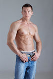 Strong man with relief body. Young athlete holding his belt Royalty Free Stock Photo