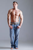 Strong man with relief body in jeans. Strong beautiful man looking at camera Stock Images