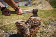 A strong man`s hand with an axe chopping wood at a camping in a mountainous region of Georgia. royalty free stock photos
