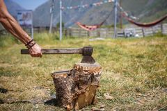 A strong man`s hand with an axe chopping wood at a camping in a mountainous region of Georgia. royalty free stock photography