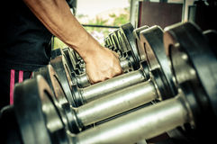 Strong man's hand takes a heavy dumbbell Royalty Free Stock Photography