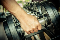 Strong man's hand takes a heavy dumbbell Stock Photo
