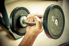 Strong man's hand takes a heavy dumbbell Stock Images