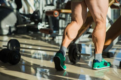 Strong man's legs. Sportsman in gym. Dumbbell and barbell on the floor in gym royalty free stock photography