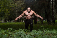 Strong Man With Samurai Sword. Action Hero Muscled Man Holding A Ancient Sword - Standing In Forest Wearing Leather Pants Royalty Free Stock Photo