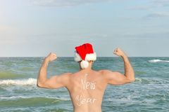 Strong man in Santa hats with the inscription New Year on the back standing on the beach. Back view Stock Image