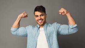 Strong man showing biceps at studio background. Happy man showing strength, strong and reliable royalty free stock photo