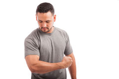 Strong man showing his muscles. Good looking athletic young man showing his arm strength against a white background Stock Images