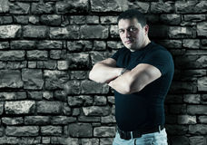 Strong man. Smilling strong male with arms crossed posing in front of brick wall. He looking at camera Stock Photo
