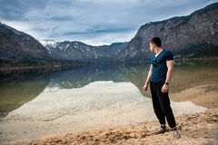 Strong man standing and relaxing near mountain lake Royalty Free Stock Images