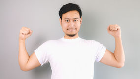 A strong man with strong pose. An asian man with white t-shirt and grey background royalty free stock photo