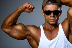 A strong man in sunglasses shows his muscles Stock Image
