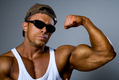 A strong man shows his muscles. Trained body. The gray backgroun Royalty Free Stock Photos