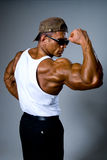 A strong man in sunglasses shows his muscles. Stock Photography