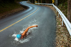 Strong Man Swim On Asphalt Road. Strong Young Man Swim On Asphalt Road royalty free stock image