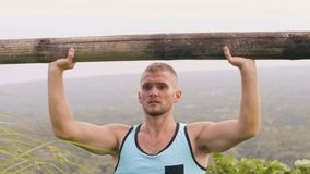 Strong man training press exercise with wooden barbell on tropical hill landscape. Bodybuilder man lifting weight with stock footage