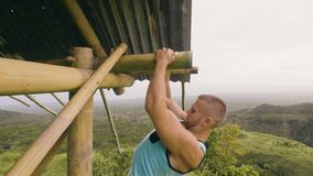 Strong man training pull up exercise on wooden bar on hill and highland covered tropical forest. Sport man pulling up on stock footage