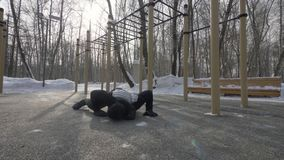 Strong man training push ups and crossfit exercise on winter sports ground. Sports man training for development strength and endurance stock footage