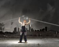 Strong man. In uniform tearing metal chain with hands stock photo