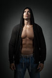Strong man wearing black hoodie isolated on dark. Background Royalty Free Stock Images
