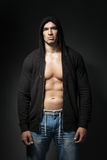 Strong man wearing black hoodie isolated on dark Stock Image