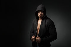 Strong man wearing hoodie isolated on black background. With copyspace royalty free stock image