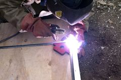 A strong man is a welder in a black T-shirt, in a welding mask and welders leathers, a metal product is welded with a welding mach. Ine in the garage, blue Stock Images