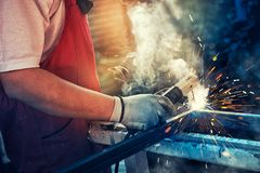 Strong man is a welder in T-shirt in a construction gloves, a metal product is welded with a welding machine in the garage. Orange sparks fly to the sides royalty free stock image