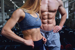 Strong man and a woman are posing with beautiful bodies. Strong men and a women are posing with beautiful bodies. Sports couple in the gym stock photography